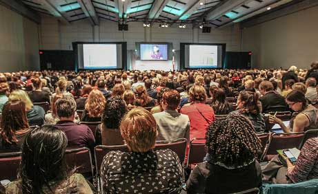 Rear view of thousands of people listening to a speaker at Health Quality Transformation, Health Quality Ontario's flagship event
