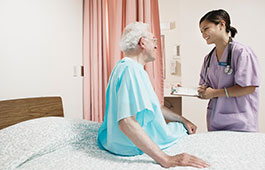 Female clinician stands bedside with an older male patient with a chart in her hand.